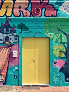 exploringthecitystreets warehouse yellowmetaldoor streetart colorful